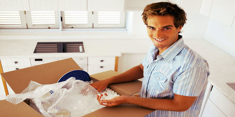 young man packing crockery for the move