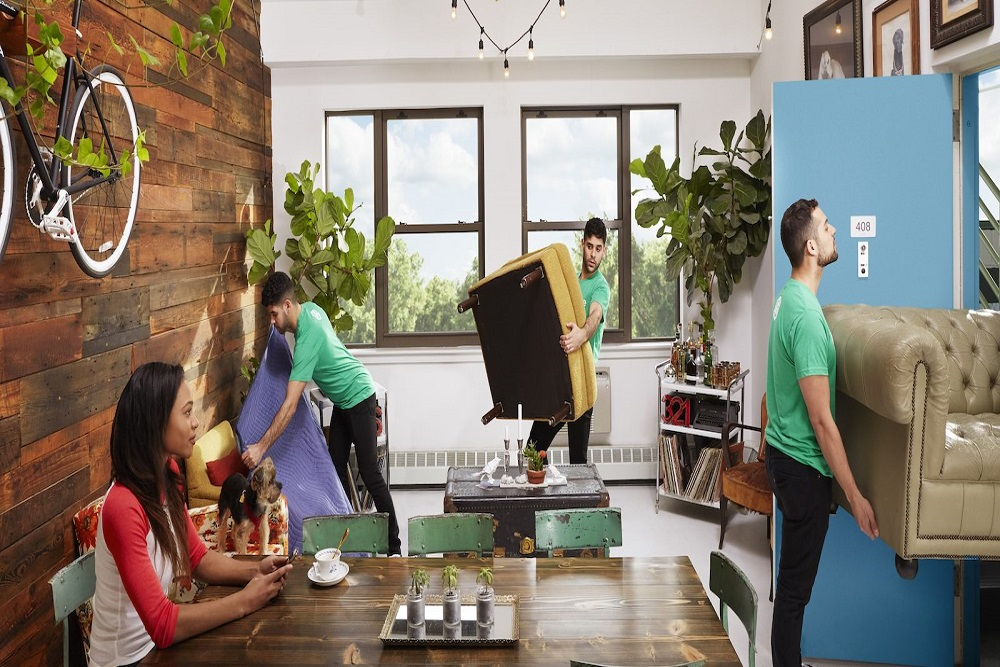 three men lifting heavy furniture out of the house and a woman sitting on chair