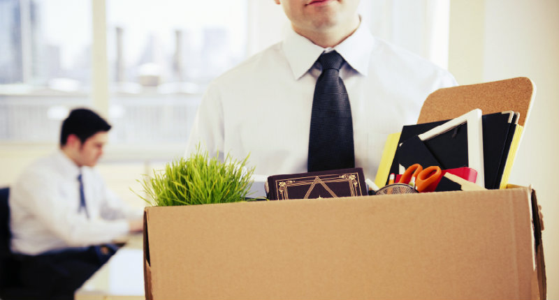 A man in suit and tie holding a box full of office items