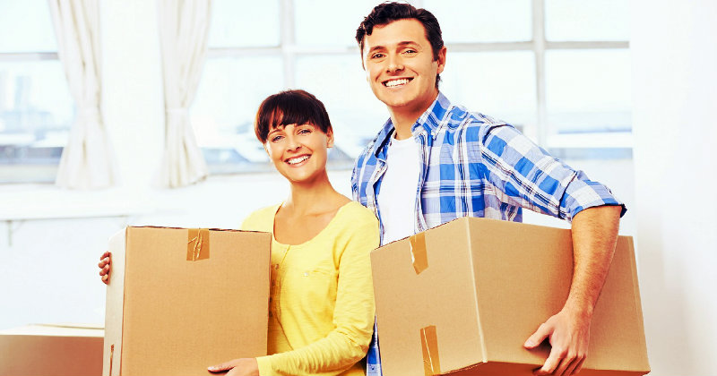 happy couple holding packing boxes in hands