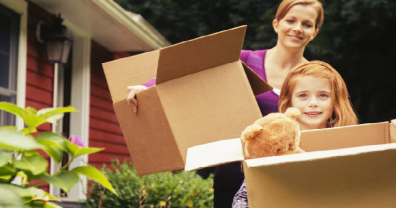 Beautiful mother and daughter carrying out boxes out of the home