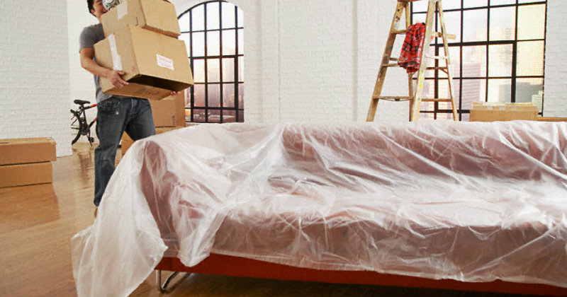 A red couch covered with plastic sheet and a man carrying packing boxes