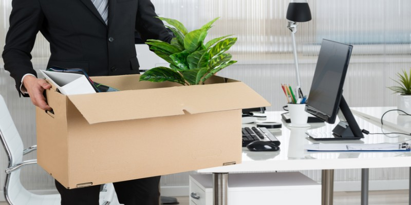 a man holding packed box with office accessories
