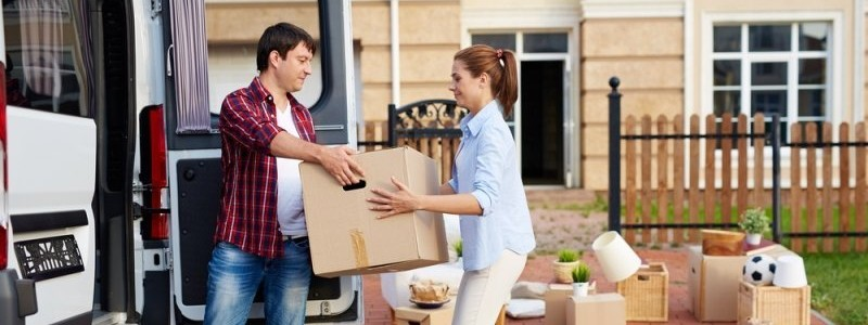 a couple is loading their household in a moving van