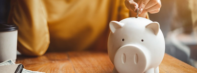 cropped picture of a woman putting a coin in a piggy bank