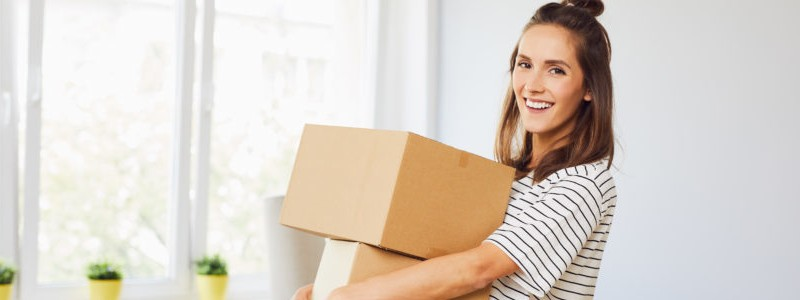 young woman holding moving boxes in her hands